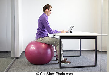 correct sitting position in office - man on stability ball...
