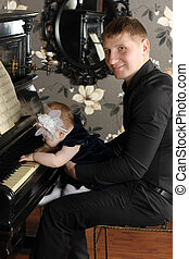 Smiling man in black with cute baby sits at piano in room....