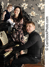 Father plays piano and sings and mother with cute baby...