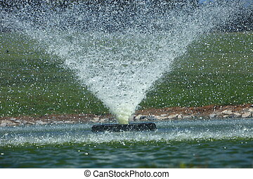 Ornamental fountain in a pond spraying out a strong conical...