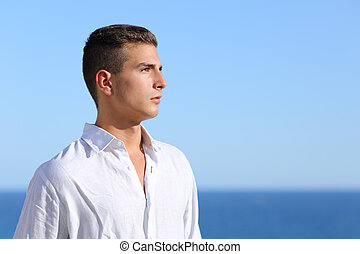 Handsome man looking at the horizon with a blue sky in the...