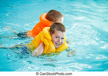 Two brothers swimming in life jacket