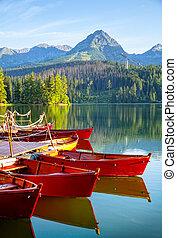 Mountain lake in High Tatra - Red boats in mountain lake in...