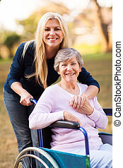 senior woman in a wheelchair and her daugther - happy senior...