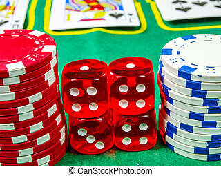 Gambling chips over green table cover with set of cards in...