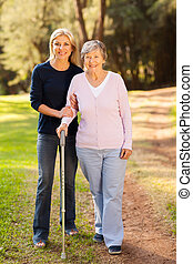 senior woman and caring daughter walking in forest - smiling...