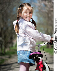little girl on her bike - Adorable girl with her bike on the...