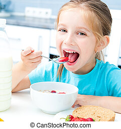little girl eating - cute little girl eating cereal and...