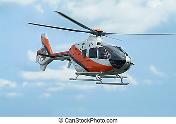Helicopter flying - Orange and silver coloured helicopter...