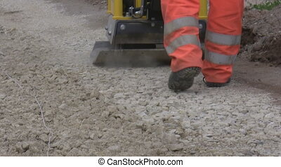 Road building machinery - A roadwork worker operating heavy...