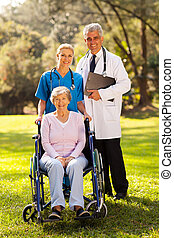 healthcare workers outdoors with disabled senior patient -...