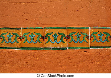 ornamental tiles in a row on orange wall
