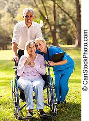 caring nurse hugging senior patient