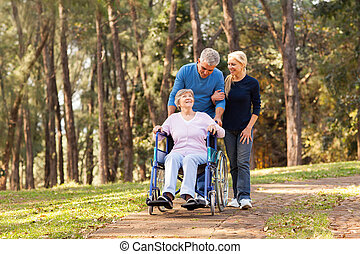 couple taking their disabled senior mother for a walk -...