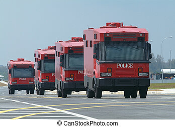 Four red police trucks - Four armoured, red police trucks,...