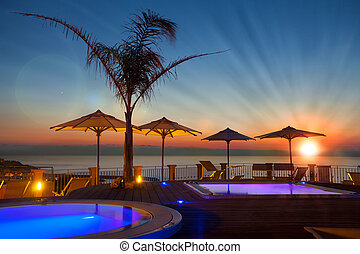 Summer time: beautiful dawn at pool area with palm and...