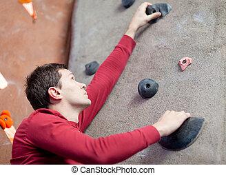 rock climbing - handsome young man rock climbing indoors