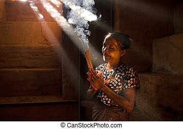 Traditional Old Asian woman praying with incense sticks inside a temple of bagan Myanmar