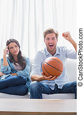 Woman looking at her husband cheering the basketball game at...
