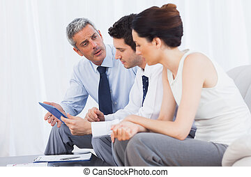Business people talking about files on sofa