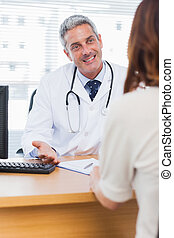 Happy doctor talking with his patient in medical office