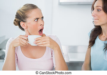 Dazed blonde looking at her friend while having tea time