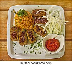 Cevapcici dish with pepper sauce - Glilled cevapcici,...