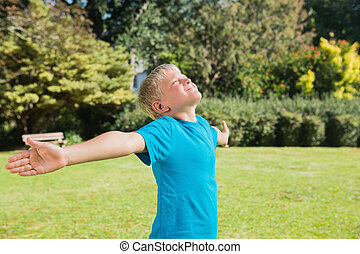 Boy stretching his arms and enjoying the sun