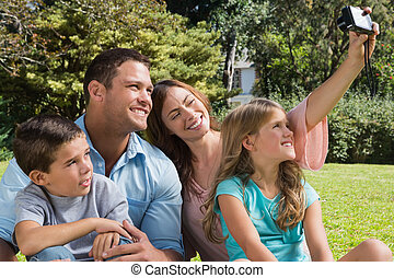 Happy family in a park taking photos