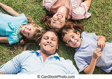 Happy family lying on the grass in a circle smiling at...