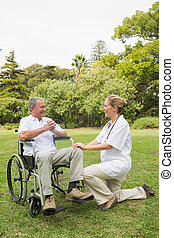 Happy man in a wheelchair talking with his nurse kneeling beside him on sunny day in the park
