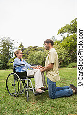Blonde woman in wheelchair with partner kneeling beside her...