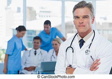 Experienced doctor posing with colleagues in background in...