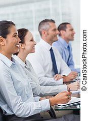 Cheerful workmates attending presentation in bright office