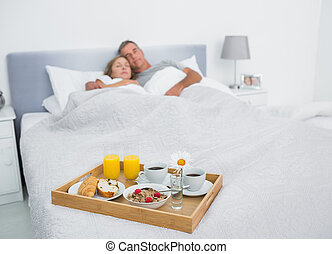 Loving couple sleeping with breakfast tray on bed at home in...