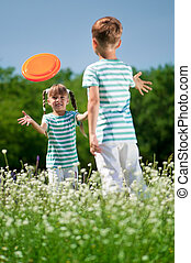 Children playing frisbee - Happy boy and little girl playing...