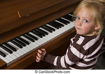 Child played on a piano - Musical child on a piano