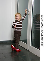 Child with big shoes opens a door
