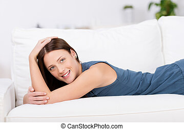 Smiling woman lying on a couch - Smiling attractive young...