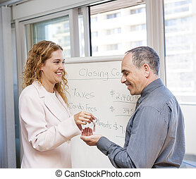 Real estate agent giving keys to client - Female real estate...
