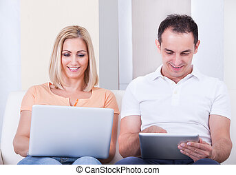 Mid-adult Couple Using Laptop And Digital Tablet