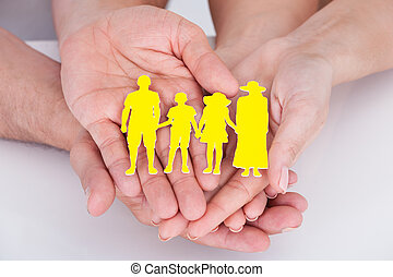 Couple holding family figure cut-out - Portrait of happy...