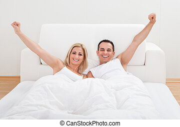 Couple Waking Up In Bed - Portrait Of Loving Couple Waking...