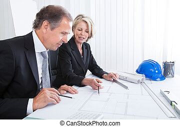 Two Architects Looking At Plans - Mature Engineers Looking...
