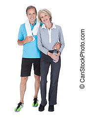 Happy Mature Couple In Fitness Attire - Man And Woman At Gym...