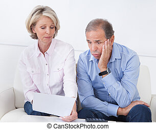 Shocked Couple Looking At Bill - Portrait Of Shocked Couple...