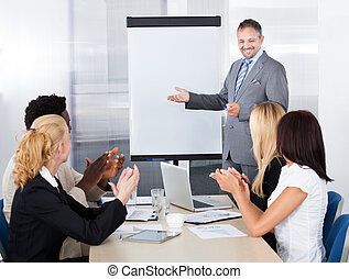 Businesspeople Clapping For A Man In Meeting