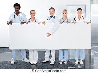 Multiracial Doctors Holding Placard - Group Of Happy...