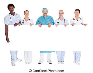 Group Of Multiracial Doctors Holding Placard Over White...