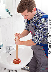 Portrait of male plumber pressing plunger in sink